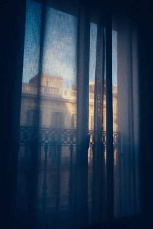 picture looking out a window through dark but still sheer curtains