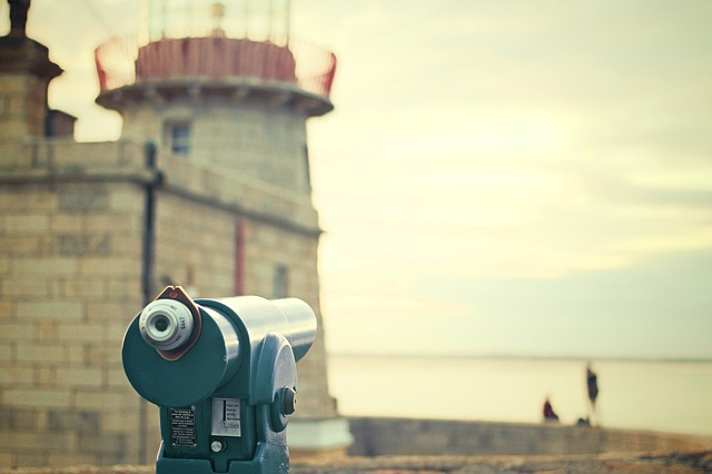 picture of a public telescope overlooking people at an old castle