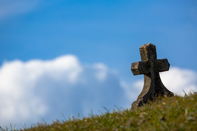 picture of gravestone (in the form of a cross) on a hill