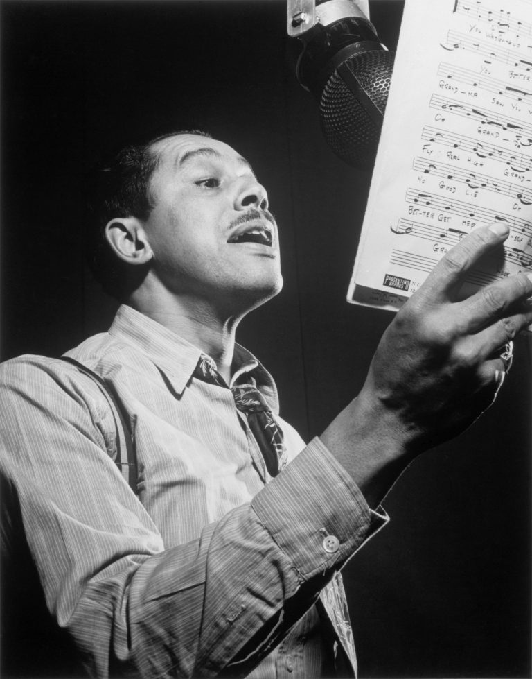 Cab Calloway holding up a sheet of music and singing