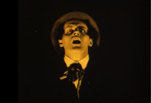 A screen shot from the film of Alan's face showing fear, with darkness all around it