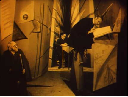 screen shot from the film of Dr. Caligari sitting in the town clerk's office