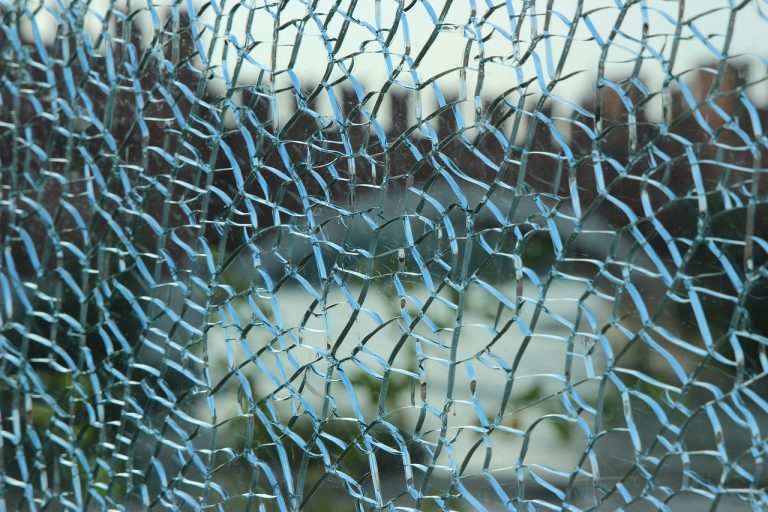 a window with spiderweb cracks of glass all over it, obscuring the view outside