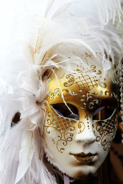 white and gold mask with many white feathers on the side and top